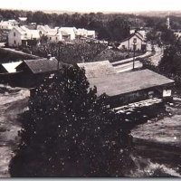 A lumber or grain mill, and beyond a cluster of mill houses.