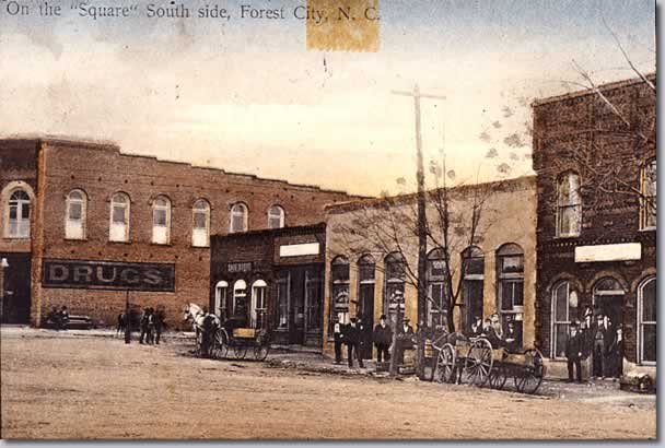 "Another tinted scene along Main Street. Titled ""On the 'Square' South Side, Forest City, N. C."" Stores, men pausing on sidewalk. Wagons along curb."