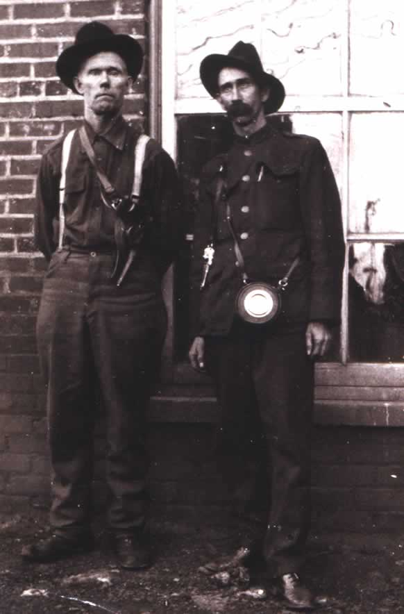 Two armed men, one in uniform with time clock over shoulder. The other with a shoulder holster holding a large pistol.