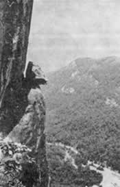 A head-shaped boulder perched on a narrow ledge high above the gorge