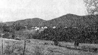 Pastoral scene with homes in the distance at the foot of the rolling mountains