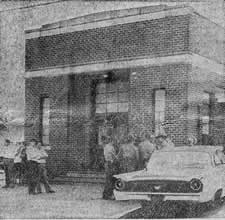 Exterior bank, cars parked, men going in front door.