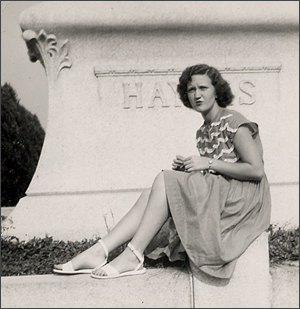 Young girl sitting on wall of Haynes tomb.