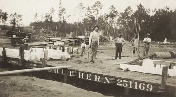 Workman standing on flatcar stopped beside cemetery. Other men in background among timbers and crates scattered on ground.