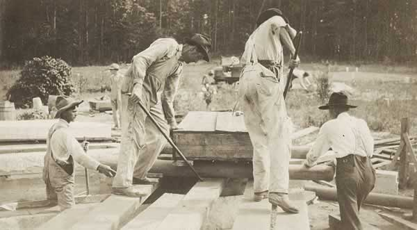 Men sliding heavy slab of stone on lumber skids.