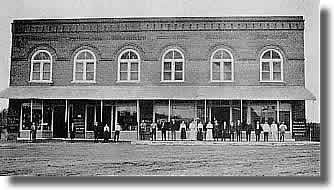 Long shot of wide store front with 15 employees lined up for the photograph.