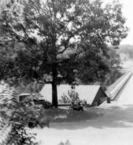 Two men reclining under the old tree at the end of the river bridge.