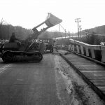 The Caterpiller front-end loader, with cables attached to its bucket, rips the side rails loose from the bridge.