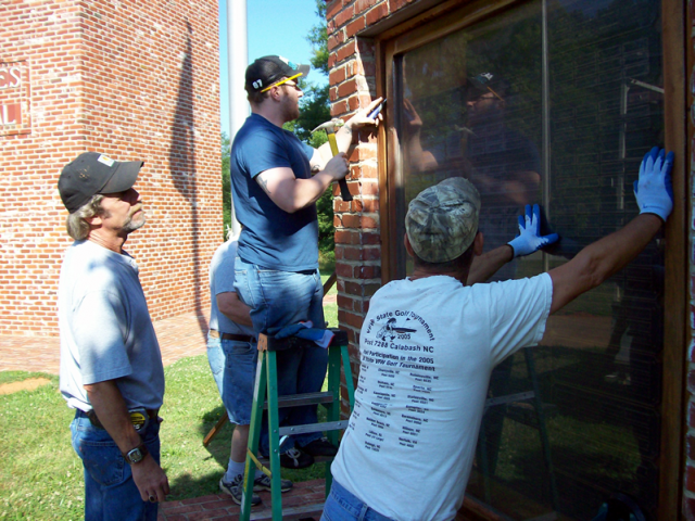 Now four men lift and insert a new pane into the structure opening.