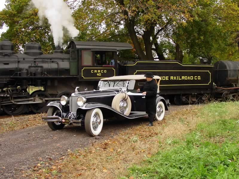 With the train stopped in the background, a man in black stands beside his elegant antique roadster.