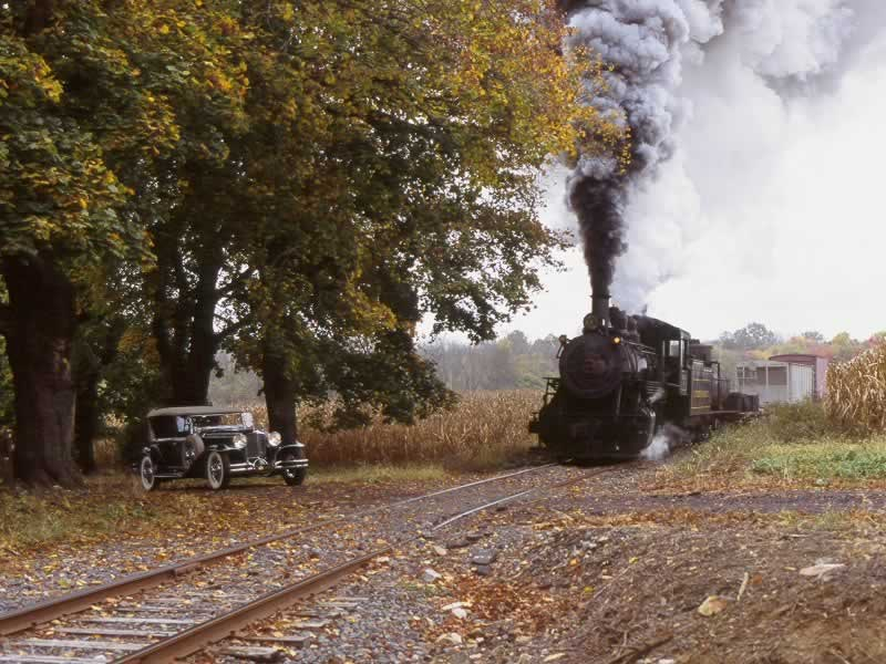 As the train approaches a little country crossing, an antique car waits for it to pass.