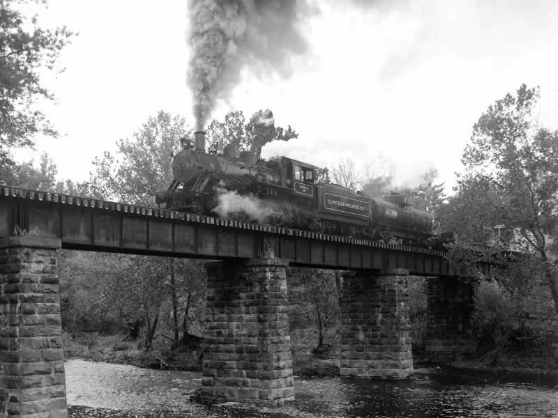 A dramatic black and white photo taken from a low angle as the train runs across an old trestle.