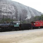 "A ""train"" assembled for the tourists. In the background is the massive stone mountain with the Civil War carving in its side."