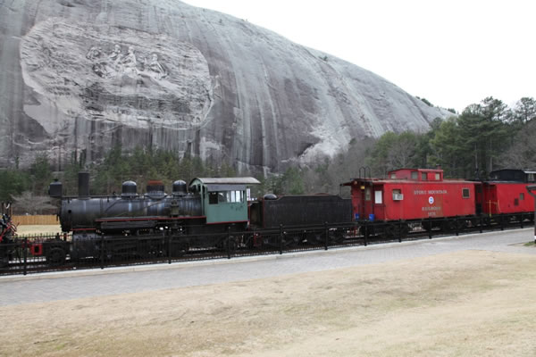 """A """"train"""" assembled for the tourists. In the background is the massive stone mountain with the Civil War carving in its side."""