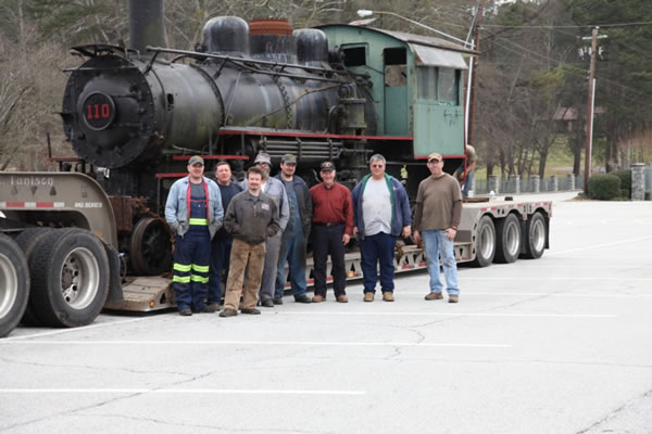 A crew of eight stand for a final photo before the engine they've been maintaining for years.