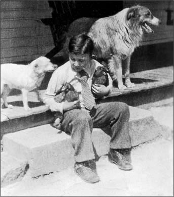 Grover, Jr. sitting on the porch step with his pets