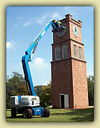 Tower with man-lift arm reaching 50-feet up to clock face.""