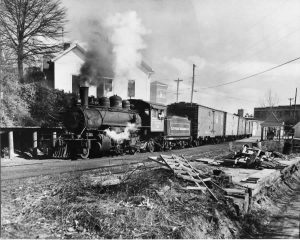 The train is under steam, leaving the mill area.