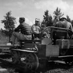 Little railroad service vehicle propelled by a small gasoline engine, pulling a small trailer. Three men on board.