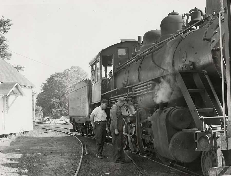 Three crewmen standing beside stopped locomotive looking at its components.