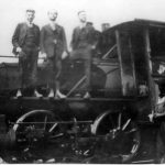 Three men in business suits standing proudly on side rail of the new acquisition