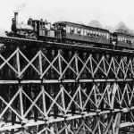Train with two packed passenger cars, stopped atop high wooden trestle