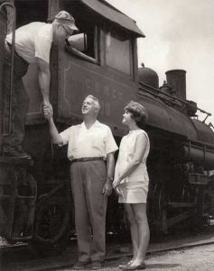 Trainman bends down from cab to shake hands with Paul Bridges, who with his daughter is standing on the ground.