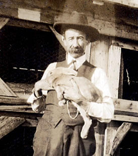 A. L. Campbell standing beside a large multi-room rabbit hutch.