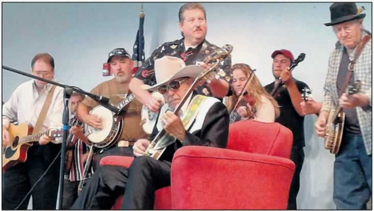 Dan, in his traditional western garb, sit in a red armchair, with six of his students stand around him. They're playing their bluegrass instruments.