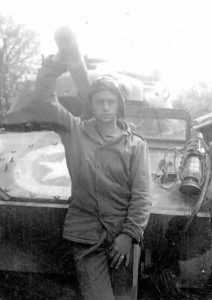 The young soldier, looking weary leans against the front of his tank.