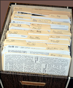 A banker's box filled with folders full of news clippings.