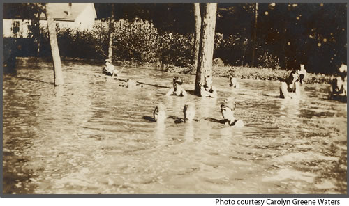 Two mothers and their kids bathing in Riddle's Creek behind the houses on Valley Street in the 1940s.