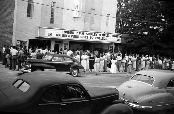 "Early evening outside Griffin Theater in Forest City.  A long line in front of box office. Late 1940s cars parked on street. The marquee reads: ""Tonight 7 p m Shirley Temple in Mr Belvedere Goes To College."""