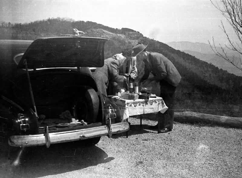 On a mountain overlook, the trunk is open on the family car. A husband, wife and another lady are gathered around a small cloth-covered folding table. They're setting out their picnic items. It's obviously chilly (even in summer, in the mountains) for the wife has on a winter coat and a kerchief.