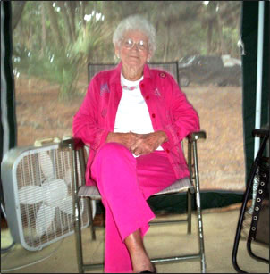 Ottie, in a stylish rose-colored pantsuit, sits in a lawn chair inside a portable screened-in gazebo at the mountain campground.