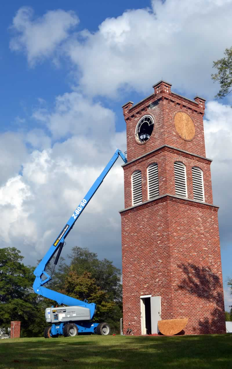 The entire tower is framed against a blue sky with majestic cloud formations. On the ground, at the tower's west side, a 60-foot power lift reaches up towards a gaping circular hole where the clock face has been removed.