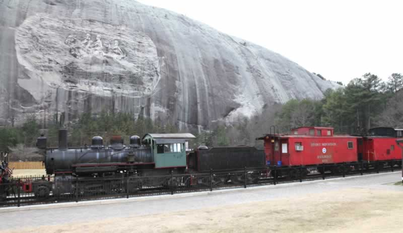 The old engine leading two cabooses (the last one an engine in a caboose's clothing). In the background is the enormous boulder called stone mountain with the famous carving in its side of Confederate generals.