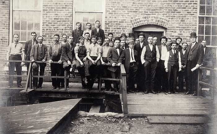 A large group of millworkers near the side entrance to Cliffside mill.