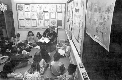A classroom setting with students seated on the floor.