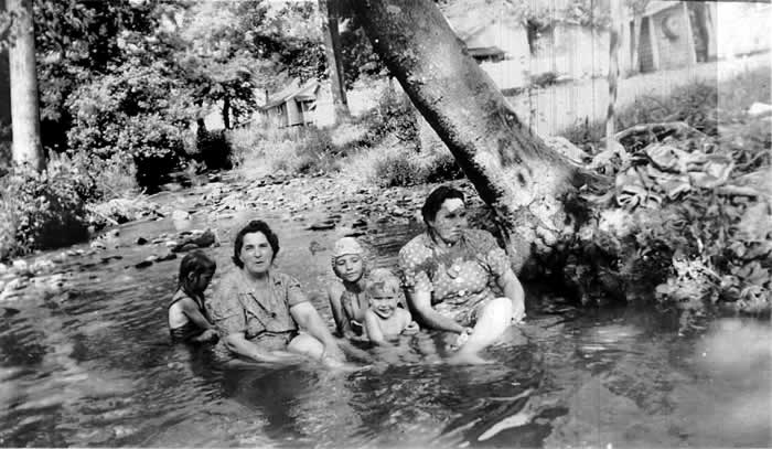 Two mothers in dresses sitting with their children in a shallow creek.