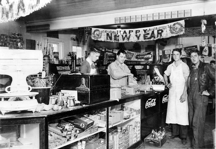 """Interior of one of Cliffside's groceries, a """"Happy New Year"""" banner hangs from the ceiling.  A long counter runs in the foreground, topped with 1943 vintage scales, cash register and other tools of the trade."""