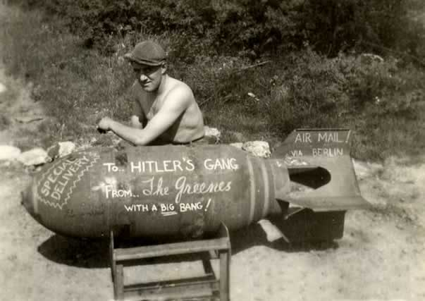 """A shirtless GI sits beside and leans on an enormous 6-foot-long bomb. Someone has written on its side {with chalk) special greetings to the enemy. """"To Hitler's Gang with a big bang! From the Greenes"""" and """"Via air mail to Berlin!"""""""