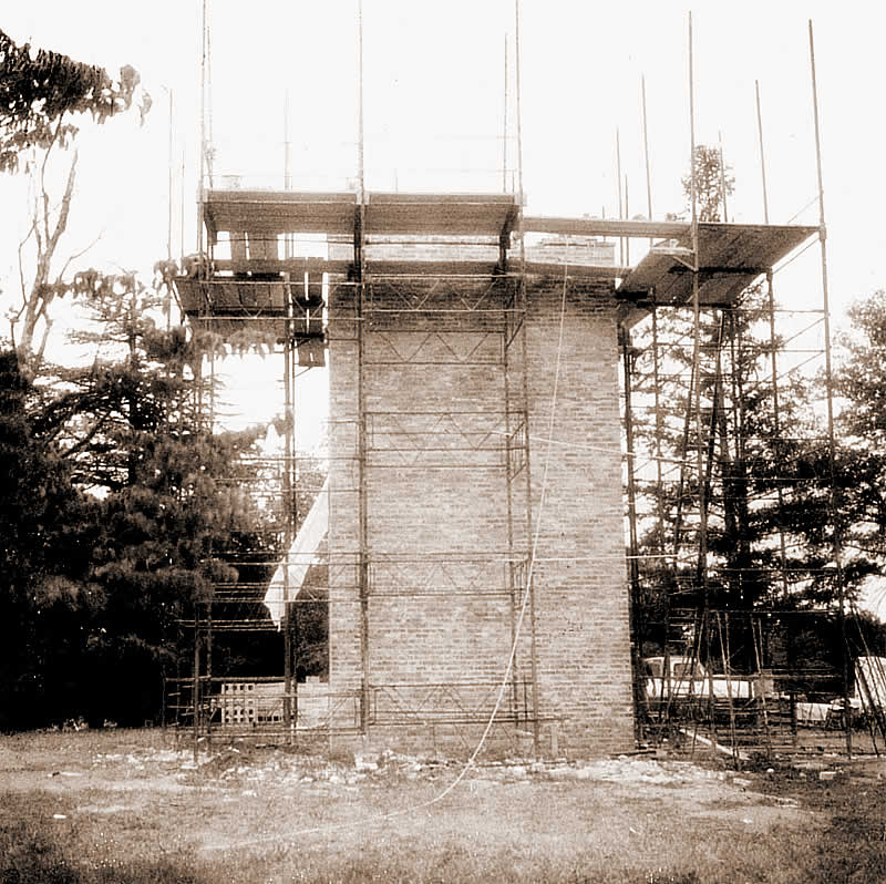 The bottom half of the tower surrounded by scaffolding. Platforms for the brick-layers at the top of the completed part, ready for their work to continue.