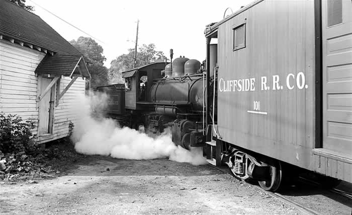 Blasting steam from its under carriage, a locomotive pushing a boxcar navigates a tight bend around an old wooden building.