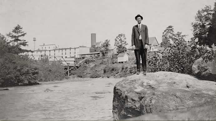 A man in a suit and tie standing on a giant boulder jutting out from the river bank. The buildings and water towers of early Cliffside can be seen behind him.