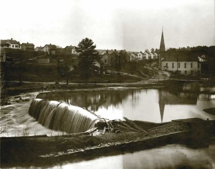 We looking over the low dam and pond at Henrietta in the early 1900's. On the far side is a narrow road curving around the high-steepled church. Beyond, alongside the road is a row of two-story mill houses.