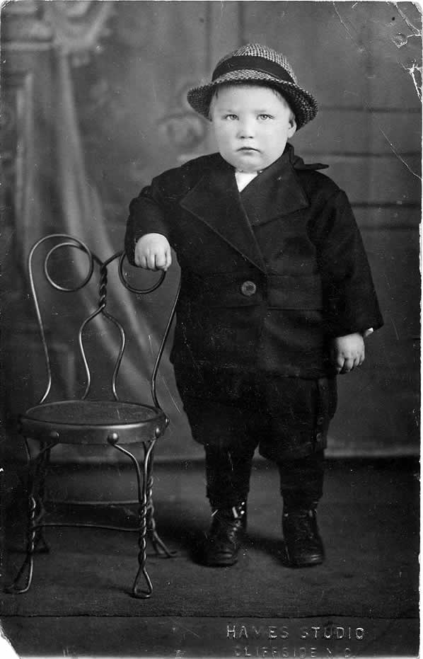 A young boy, about three or four, stands stiffly in the photographer's studio, grasping the top of a prop wire-frame chair. A painted backdrop is behind him. He's dressed like a little man, in a double-breasted suit, even a hat. He glares at the photographer.