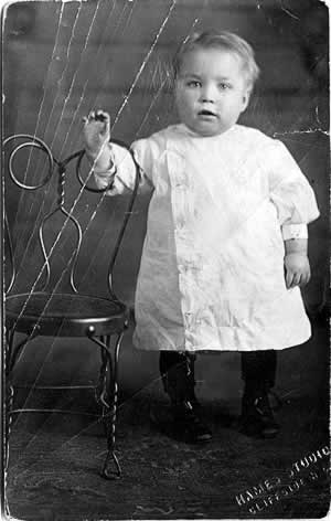 A different child, perhaps two, standing in the same setting as the boy in the photo above. He's wear a child's smock buttoned up the front and fitting tightly on his neck and pudgy wrists.
