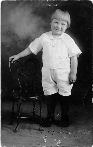 Another studio photo, same chair and perhaps the same boy as above, but older. In this one he's smiling.