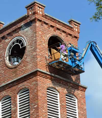 On the south side of the tower, workmen on the power lift are covering the empty clock face hold with circles of plywood.